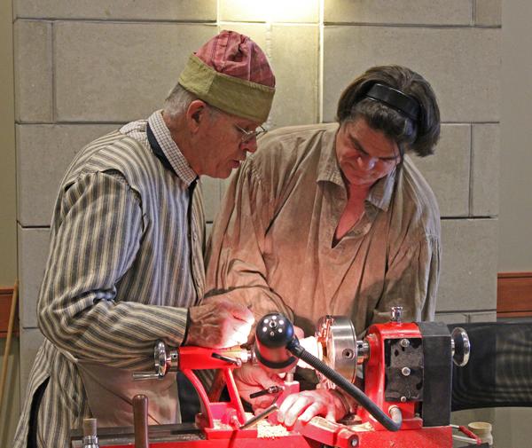Erv Tschanz, Master Horner (left) instucts Fred Noesner on lathe work.